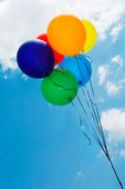 Low angle view of balloons in the sky forming a rainbow flag